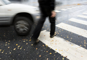 Man on pedestrian crossing in autumn, in danger of being hit by car
